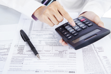 Man using calculator filling out tax forms