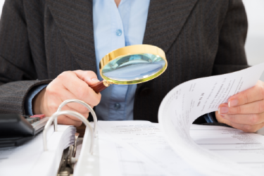 IRS Agent using magnifying glass to read tax return