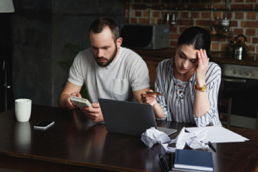 a frustrated couple paying bills